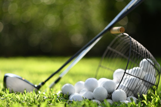 Golf balls in basket and golf clubs on green grass for practice