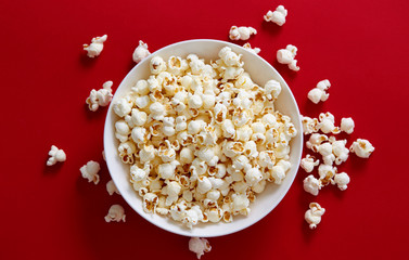 Popcorn in a white bowl against red background
