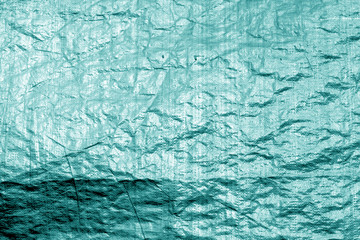 Crumpled transparent plastic  surface in cyan color.