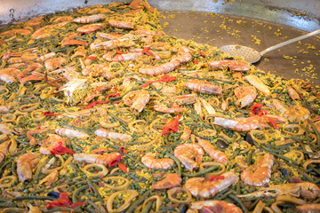 Large pan of paella in a street tray with food