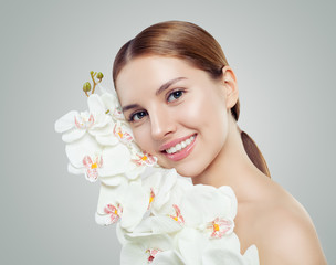 Young smiling woman with healthy skin and white orchid flowers