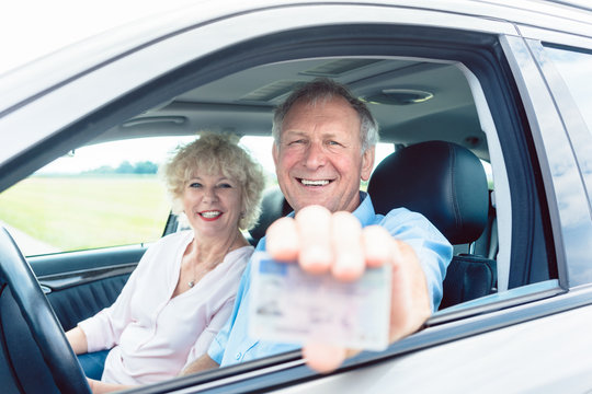 Portrait of a happy senior man showing his available driving license while sitting in the car next to his cheerful wife
