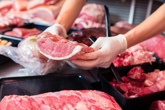 Meat in a butcher shop display being put in by sales woman, close-up