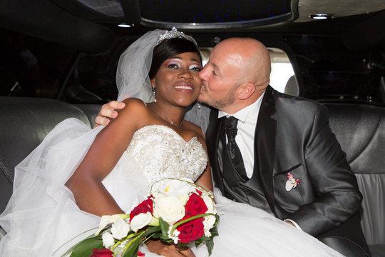 happy caucasian man groom kissing her charming wife bride black african in luxury wedding car