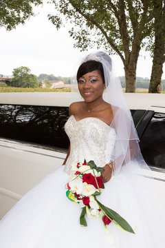pretty bride african american woman in weddin day with white limousine car