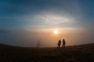 silhouette of people on top of mountain at sunrise