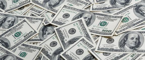 A background of scattered hundred dollar bills.