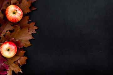 Autumn nature concept. Background with autumn symbols. Brown leaves and appleon black background top view copy space pattern