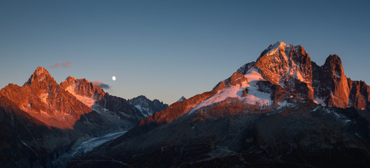 Fotomurales - Panorama of the last sunlight on the mountain peaks near Chamonix, France, during moonrise.