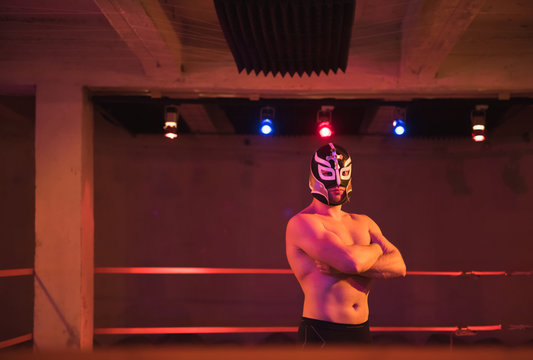 Confident man in wrestling mask on ring