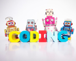 Fototapete - a team of toy robots with the word coding isolated