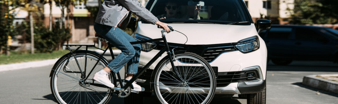 partial view of woman riding bicycle while crossing road with driver in car