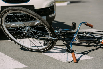 close up view of broken bicycle and car on road, car accident concept