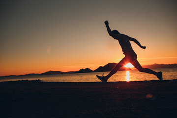 Young energetic happy man jumping on the seashore