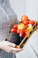 Senior woman holding a box with vegetables in hands.