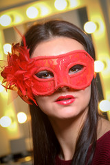 Beauty model woman wearing masquerade carnival mask over Christmas and New Year celebration holiday party