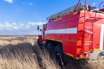 Red firetruck car Ural rides through the autumn field with yellow and faded grass against the blue sky and clouds. The concept of extinguishing forest fires in USA