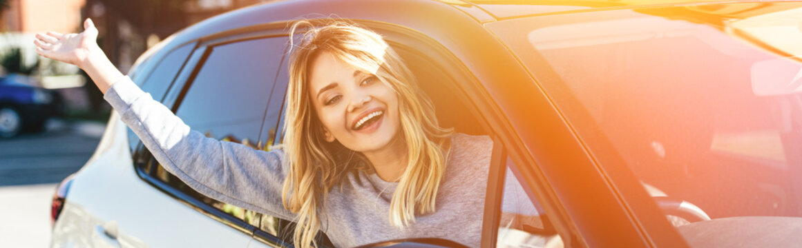 portrait of happy blond woman waving to someone while driving car