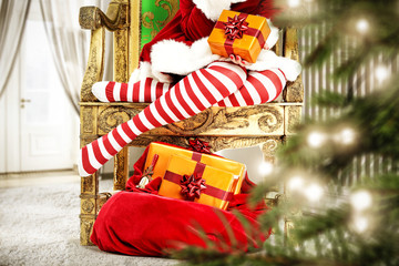 Slim young woman legs in christmas tights. Christmas tree and gifts. Home interior with big window.