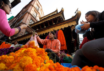 A street vendor sells garlands made of marigold flowers along the streets during the Tihar festival, also called Diwali, in Kathmandu