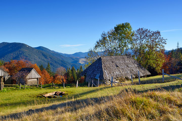 Beautiful landscape with old wooden hut in the Carpathians mountains. Autumn sunny day.
