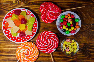 Colorful chocolate candies, lollipops and jelly sweets on wooden table