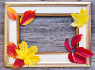 Autumn composition. A light picture frame with fall leaves on old wooden background. Top view.