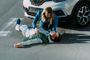 Obraz high angle view of scared young woman touching injured man lying on road after car accident - fototapety do salonu