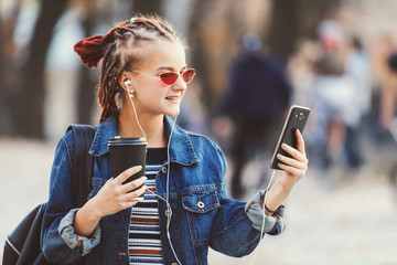 Portrait of hipster cute girl with dreads wearing headphones and glasses drinking coffee and laughing while swiping pages on her smartphone