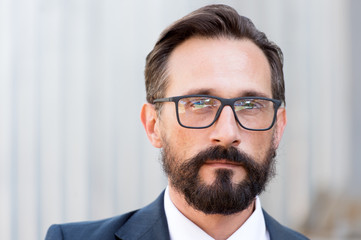 Close up of calm man wearing glasses and looking at you