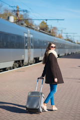 Happy young woman wearing glasses dressed in coat with big travel bag at the railway station on the train background