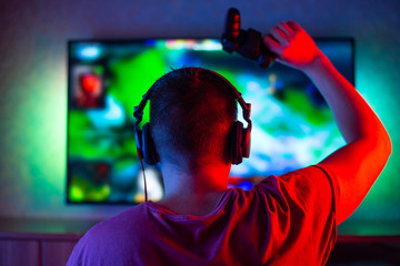 Gamer or guy-streamer at home in a dark room with a gamepad playing with friends in networks in video games. A young man is sitting in front of a monitor or TV.