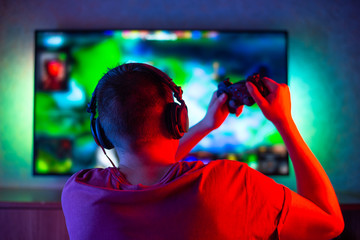 A gamer or streamer in headphones and a geypad sits at home in a dark room and plays with friends in networks in video games. A young man is sitting in front of a monitor or TV.