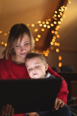 Mother and son using digital tablet with Christmas lights in