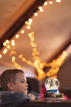 Boy looking at Christmas tree snow globe