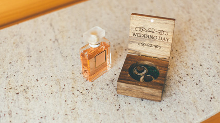 Engagement rings and a bottle of perfume, wedding accessories closeup