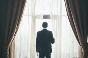 Groom is standing in front of curtained window