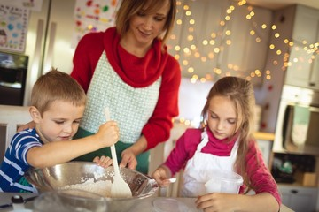 Mother and kids making Christmas cookies in kitchen