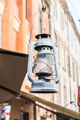 Still life of old hurricane lamp on the street. Reportage photo. Vintage lamp. Kerosene lamp. Old-fashioned equipment. Ancient decorations. Retro gas lamp.