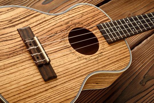 tenor ukulele made of zebrawood on aged wood background