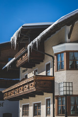 Traditional tyrolean house with wooden balconies and huge icicles in Seefeld on sunny winter day