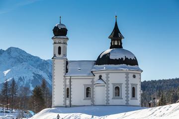 landmark Seekirchl church in Seefeld covered in snow on sunny winter day