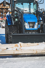 Blue dredge on sunny winter day shovels snow covered wood planks
