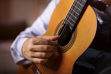 Close up of guitarist hand with long fingersnails on classical guitar. Selective focus, shallow depth of field.