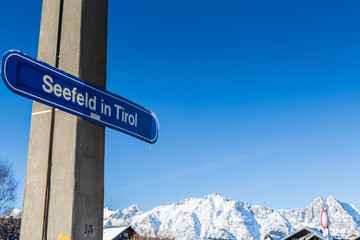 Seefeld gateway sign with snow covered mountains in the background