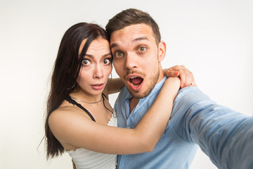 Funny couple posing and making selfie photo on white background