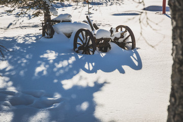 Traditional wooden machine with wheels covered in snow on sunny winter day