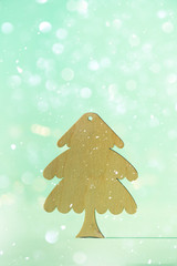 Greeting card in minimal style. Wooden Christmas tree on blue background with copy space, lights...