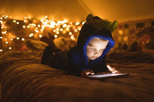 Boy in jacket using digital tablet while lying on bed at home