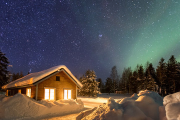 Winter landscape with wooden house under a beautiful starry sky and Northern Lights